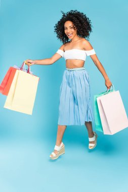 Excited african american girl holding shopping bags and walking on blue stock vector