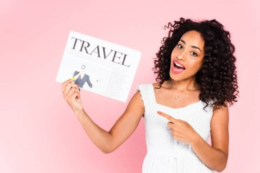 Curly african american woman pointing with finger at travel newspaper isolated on pink stock vector