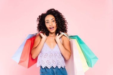 Surprised african american girl holding shopping bags isolated on pink stock vector