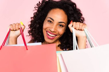 Smiling african american woman holding shopping bags isolated on pink stock vector