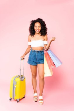Cheerful african american woman standing with luggage and holding shopping bags on pink stock vector