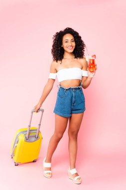 Cheerful african american woman holding cocktail and walking with suitcase on pink stock vector