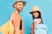glückliche Reisende in Hüten, die vereinzelt auf blauem Grund in die Kamera schauen