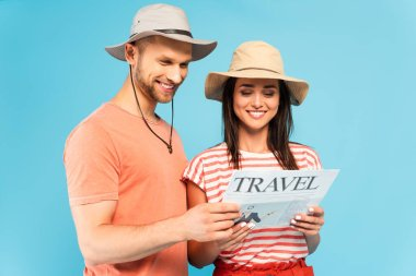 Happy couple reading travel newspaper isolated on blue stock vector