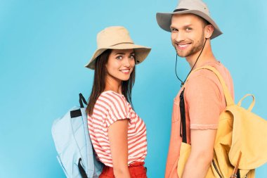 Happy couple in hats with backpacks looking at camera isolated on blue stock vector