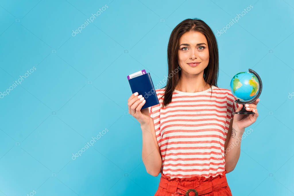 Attractive girl holding passport and globe isolated on blue stock vector