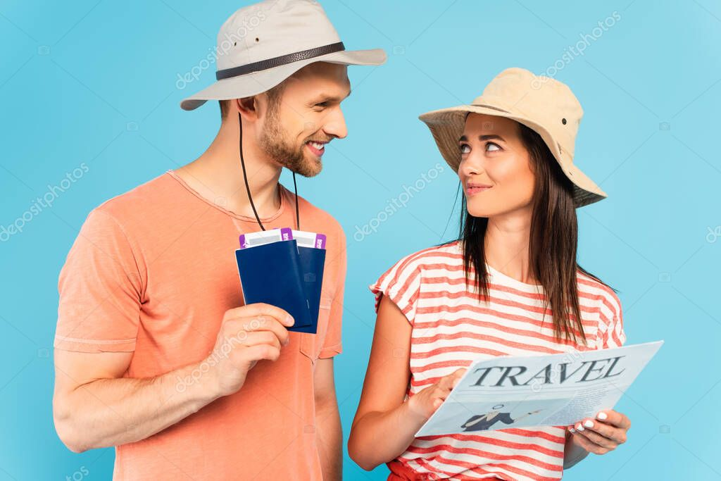 Happy girl in hat holding travel newspaper and looking at man with passports isolated on blue stock vector