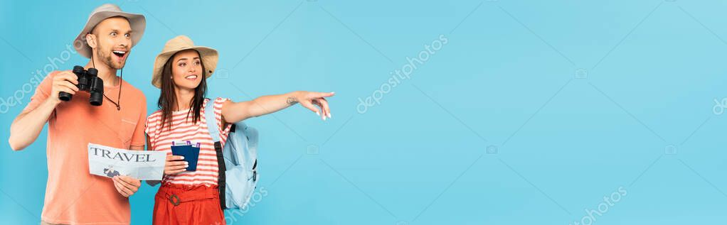 Horizontal crop of happy girl pointing with finger and holding passports near man with travel newspaper and binoculars isolated on blue stock vector