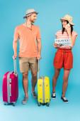 vousatý muž stojící se zavazadly a při pohledu na šťastnou dívku číst cestovní noviny a mluvit na smartphone na modré