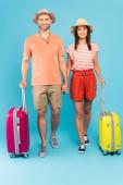 šťastný pár v klobouky stojící v blízkosti cestovní tašky a drží se za ruce na modré