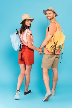 Happy couple with backpacks holding hands and looking at camera on blue stock vector