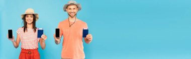 Panoramic shot of happy couple in hats holding smartphones with blank screen and passports isolated on blue stock vector