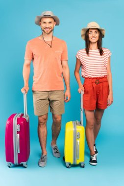 Happy couple in hats standing near travel bags on blue stock vector