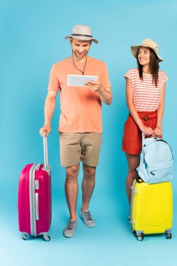 Happy girl in hat looking at man using digital tablet while standing near luggage on blue stock vector