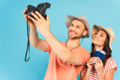 happy man in hat holding vintage camera and taking selfie with cheerful girl isolated on blue