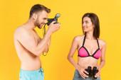 glücklicher Mann fotografiert Mädchen im Badeanzug mit Fernglas isoliert auf gelb