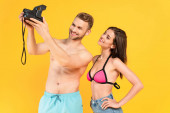 glücklicher Mann ohne Hemd macht Selfie mit Frau auf Vintage-Kamera isoliert auf gelb