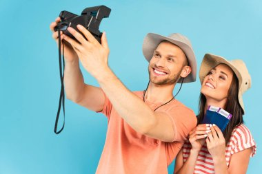 Happy man in hat holding vintage camera and taking selfie with cheerful girl isolated on blue stock vector