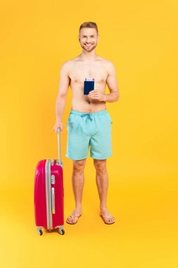 Happy and muscular man holding passport and standing with baggage on yellow stock vector