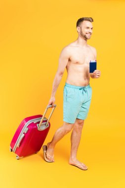 Happy and muscular man holding passport and walking with baggage on yellow stock vector