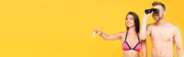 Website header of cheerful woman pointing with finger while shirtless man looking through binoculars isolated on yellow stock vector