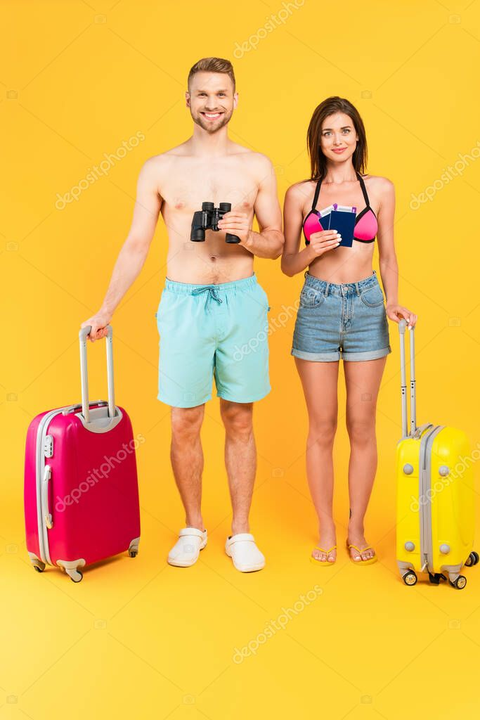 Happy couple with binoculars and passports standing near luggage on yellow stock vector