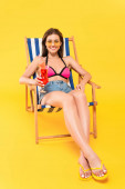 cheerful woman in sunglasses and flip flops sitting on deck chair and holding cocktail on yellow