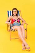 veselá žena v slunečních brýlích a žabkách sedí na lehátku a drží koktejl na žluté