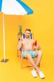 veselý muž bez košile sedí na lehátku s koktejlem a ananasem v blízkosti plážového deštníku na žluté