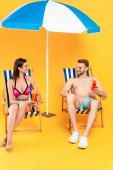 glückliches Paar in Sonnenbrille mit Cocktails, während es auf Liegestühlen in der Nähe von Sonnenschirm auf gelb sitzt