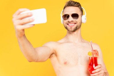 Selective focus of cheerful and shirtless man in sunglasses and headphones taking selfie while holding cocktail isolated on yellow stock vector