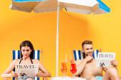šťastný pár čtení cestovních novin a posezení na lehátka na žluté
