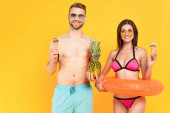 happy muscular man with pineapple near woman in sunglasses holding ice cream while standing with inflatable ring isolated on yellow