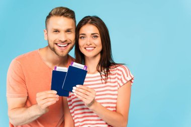 Happy couple holding passports with air tickets isolated on blue stock vector
