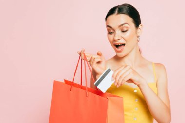 Heyecanlı esmer kadın kredi kartını alışveriş çantasına koyuyor.