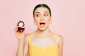 Photo shocked brunette young woman holding box with engagement ring isolated on pink