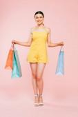 plná délka pohled na brunetky mladé ženy s nákupními taškami na růžové