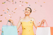 brunetka mladá žena s nákupními taškami pod pádu konfety izolované na růžové