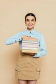 student v džínové košili s knihami na béžové