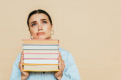 sad student in denim shirt with books isolated on beige