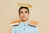 Photo skeptical student in denim shirt with books on head and shoulders isolated on beige