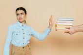 Trauriger Student im Jeanshemd mit Stop-Geste in der Nähe von Büchern auf Beige