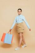 plná délka pohled na brunetky žena v džínové košili chůze s nákupními taškami na béžové