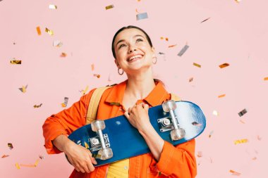 Brunette young woman in colorful outfit with skateboard under falling confetti isolated on pink stock vector