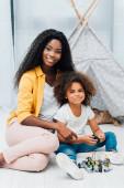 Afroamerikanische Mutter und Kind sitzen auf dem Boden neben Plastikspielzeug