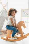 curly african american kid sitting on wooden rocking horse at home