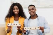 Afrikanisch-amerikanischer Mann und brünette Frau mit Holzwürfeln mit glücklichem Familienaufdruck