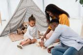 Afričtí američtí rodiče sedí na podlaze poblíž syna a dotýkají se dřevěných kostek
