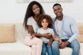 african american family looking at camera and sitting on sofa in living room