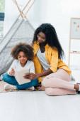 africký americký matka a dcera sedí na podlaze a čtení knihy